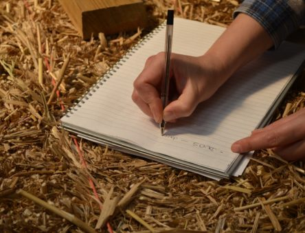 Student writing notes on top of a straw bale