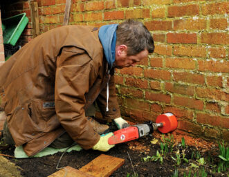 Hole being drilled in a wall to allow hedgehogs to get through